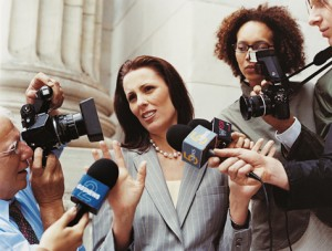 News Reporters Interviewing a Woman in a Suit Accompanied by Photographers